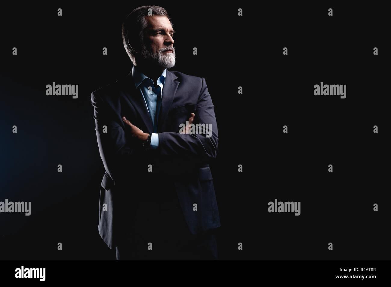 Apuesto hombre de negocios maduro aislado sobre fondo negro Foto de stock