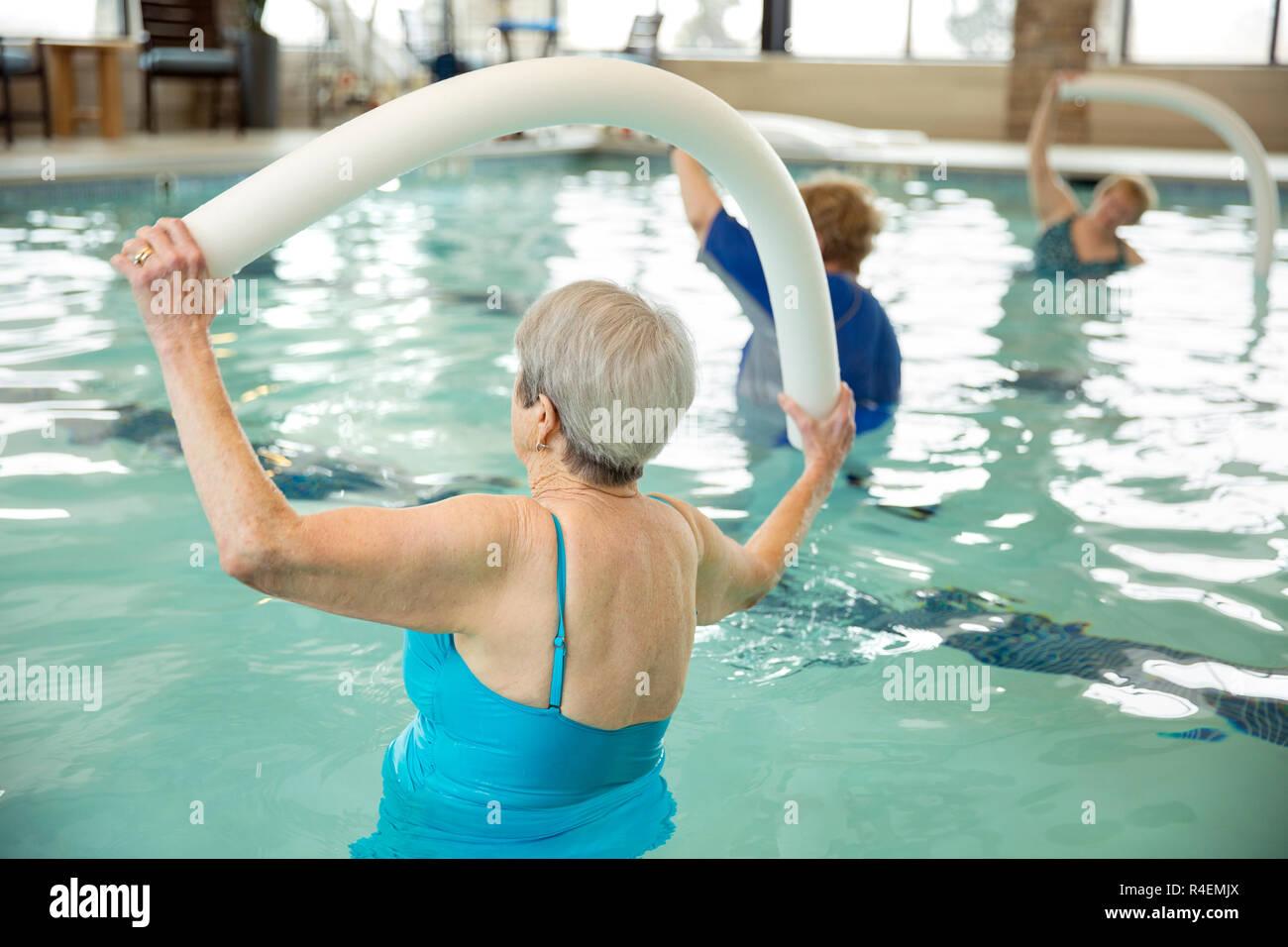 Las mujeres mayores ejercicios con ejercicios aeróbicos en el agua Imagen De Stock