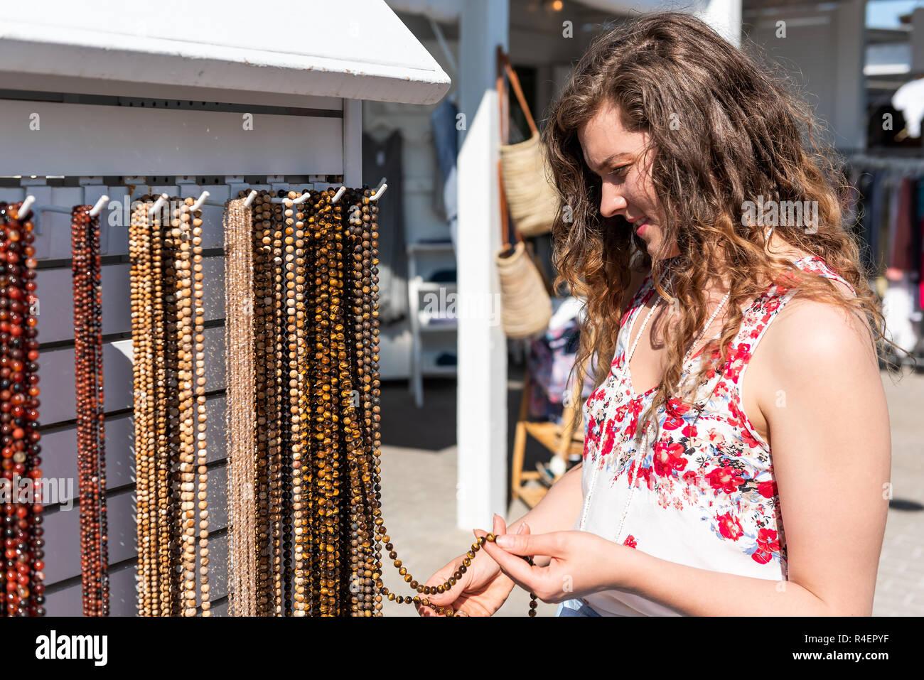 5f901a0aba40 Mujer joven para compras de playa de piedra coloridos Collares Joyería  tocando la mano en el