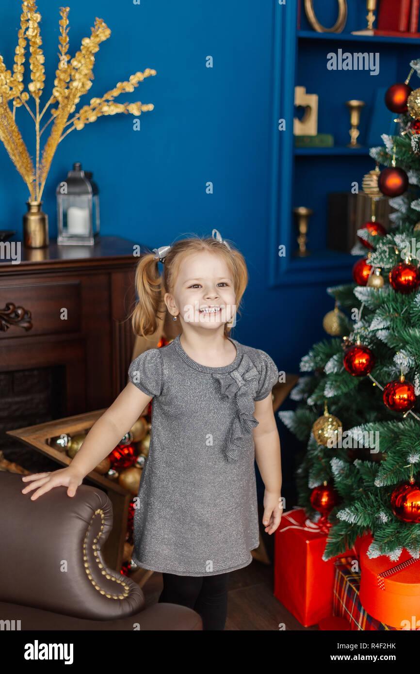56ca07c5ac Muy hermosa niña de pie en el árbol de Navidad con regalos. Imagen De Stock
