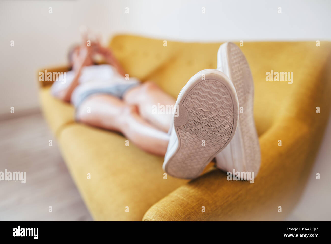 Mujer joven relajante para dormir en el sofá en casa. Se centran en pie. El concepto de descanso Foto de stock