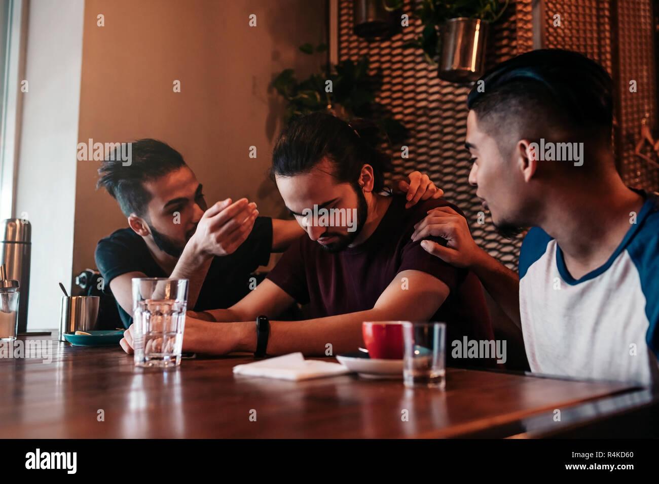 Los hombres jóvenes de apoyo animan a sus desolados amigo. Arabian chicos animarle y aconsejarle en el restaurante. Concepto de amistad. Imagen De Stock