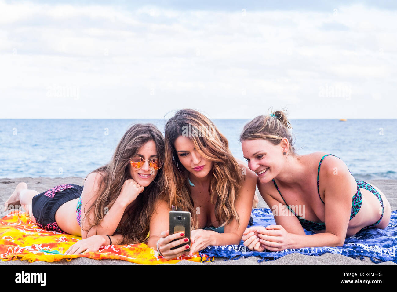 Grupo de tres chicas guapas amistad estancia sentar relajado en la playa hablando y utilizando un smartphone para compartir su vida con verano fri Foto de stock