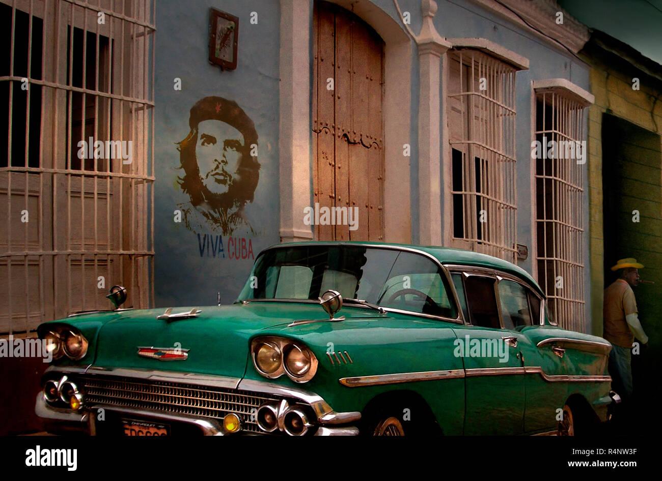 Coches Antiguos y graffiti del Che Guevara en la calle Trinidad, Provincia SpritusSanctiÂ, Cuba Foto de stock