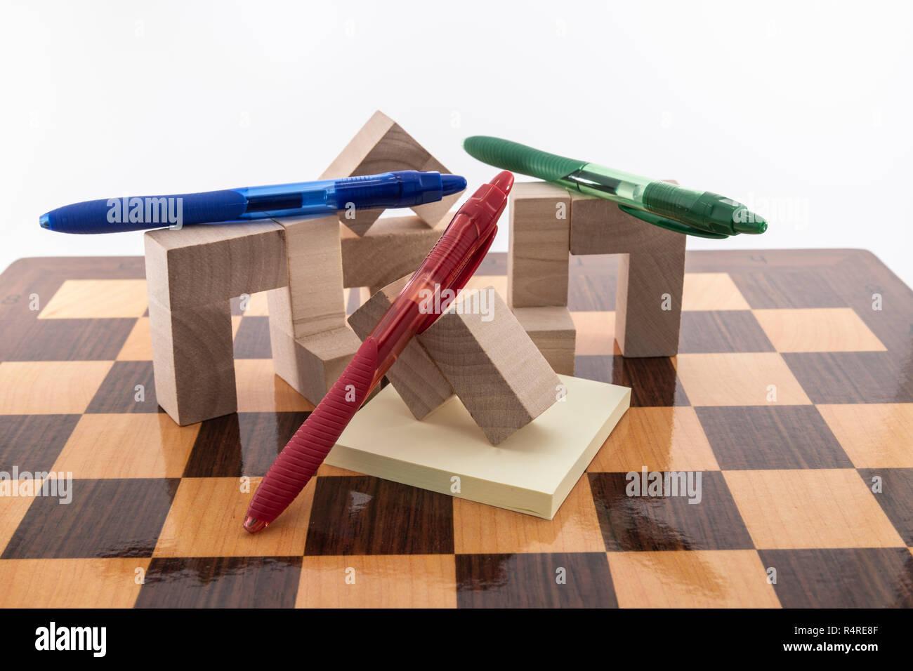 Un tablero de ajedrez y lápices de colores, colocado sobre un fondo blanco, Foto de stock