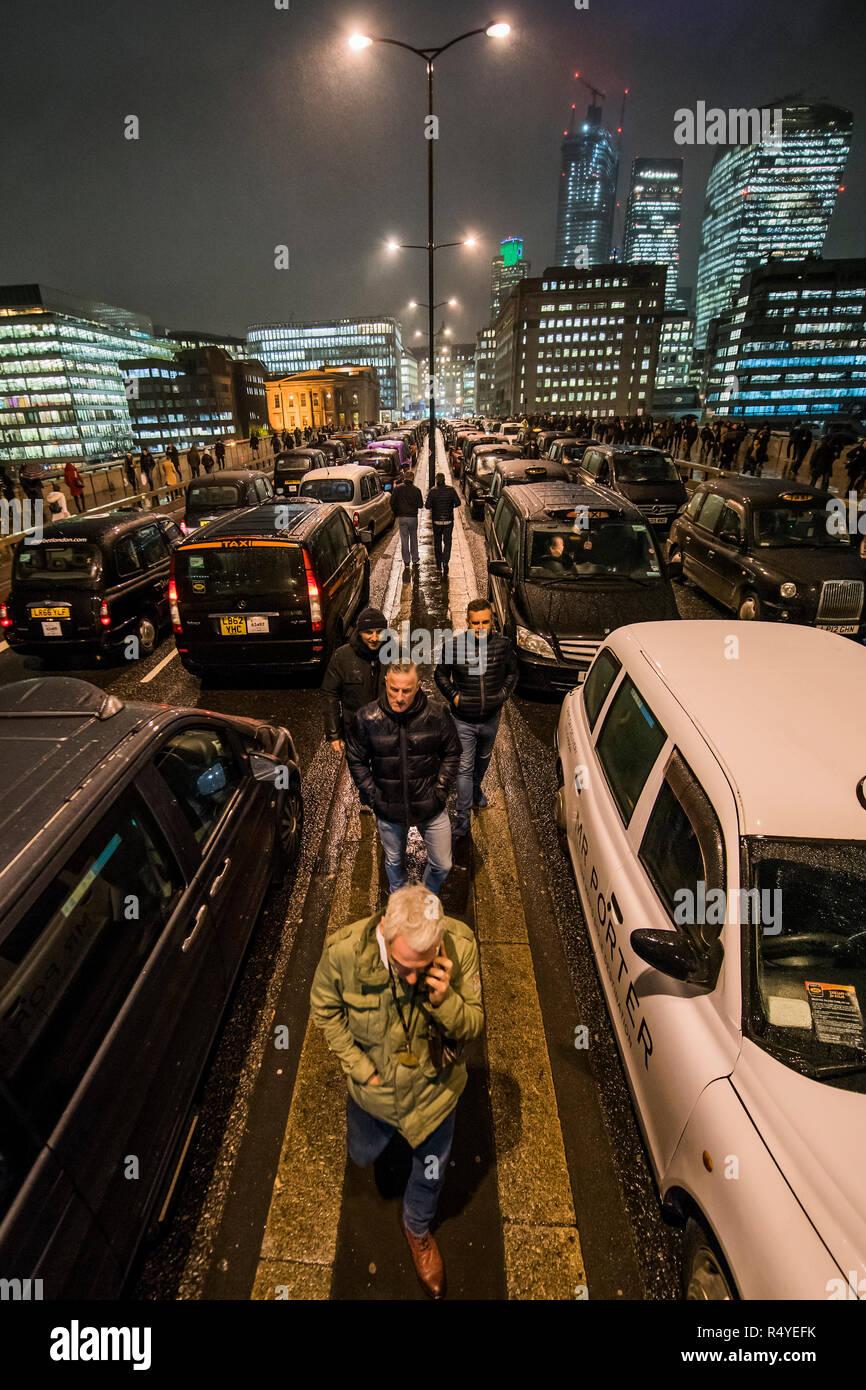 Londres, Reino Unido. 28 Nov, 2018. Los taxis negros de Londres bloque de puente para una tercera noche, y a pesar de la miserable clima, como parte de su taxi con licencia y protestar contra la decisión de TfL para bloquearlos de conducción, donde los autobuses son permitidos - como en Tooley Street y Bnak Junction. Crédito: Guy Bell/Alamy Live News Imagen De Stock