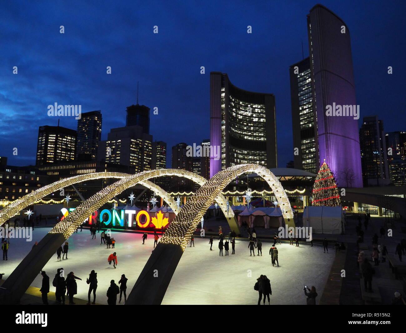 Pista de patinaje con las luces de Navidad y lit Toronto firmar, por la tarde delante de la moderna Toronto City Hall Imagen De Stock