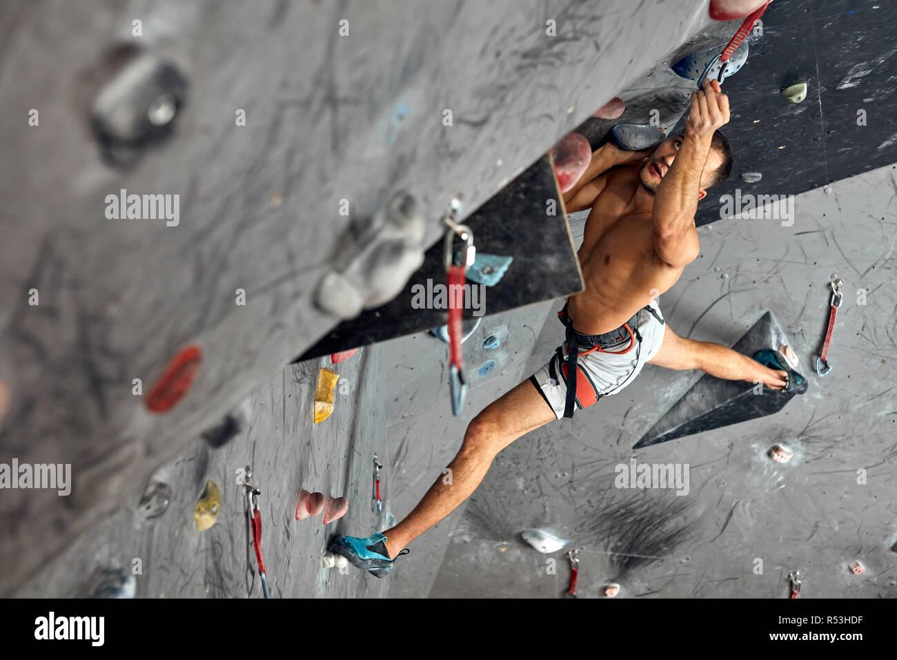 Trepador profesional masculino en Indoor Workout a trepar rocas centro. Foto de stock