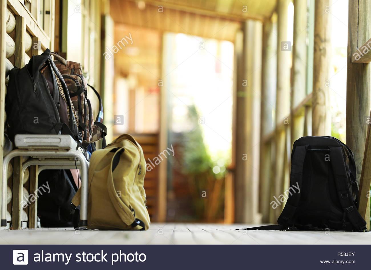 Varias mochilas escolares, mochilas, bolsos de tela fuera del aula en una escuela secundaria de pasillo al aire libre. Patio de la escuela de medio ambiente. Imagen De Stock