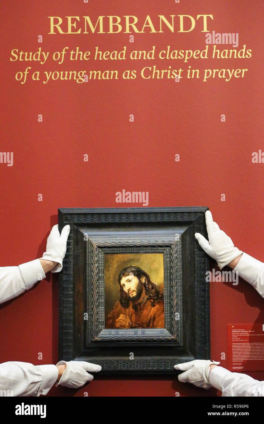 """Sothebys. Londres, Reino Unido. 30 Nov 2018 - Técnicos colgar un boceto de aceite """"estudio de la cabeza y juntaban las manos de un joven como Cristo en oración circa 1655' de Rembrandt Harmensz van Rijn (est £6.000.000 - 8.000.000 libras). Este está apareciendo en el mercado por primera vez en 60 años, y por primera vez desde las huellas dactilares, pensado para ser los de la artista, fueron descubiertos ocultos en el trabajo. Las obras maestras que se extiende a lo largo de dos milenios compuesto de viejos maestros y pinturas británicas previsualizar en Sothebys. Crédito: Dinendra Haria/Alamy Live News Imagen De Stock"""