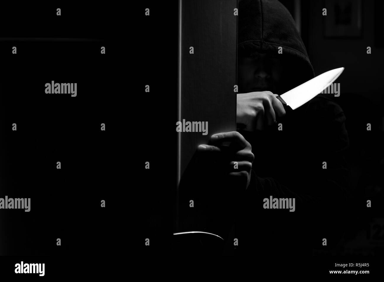 Fotografía en blanco y negro de asesino con cuchillo en apartamento oscuro Foto de stock