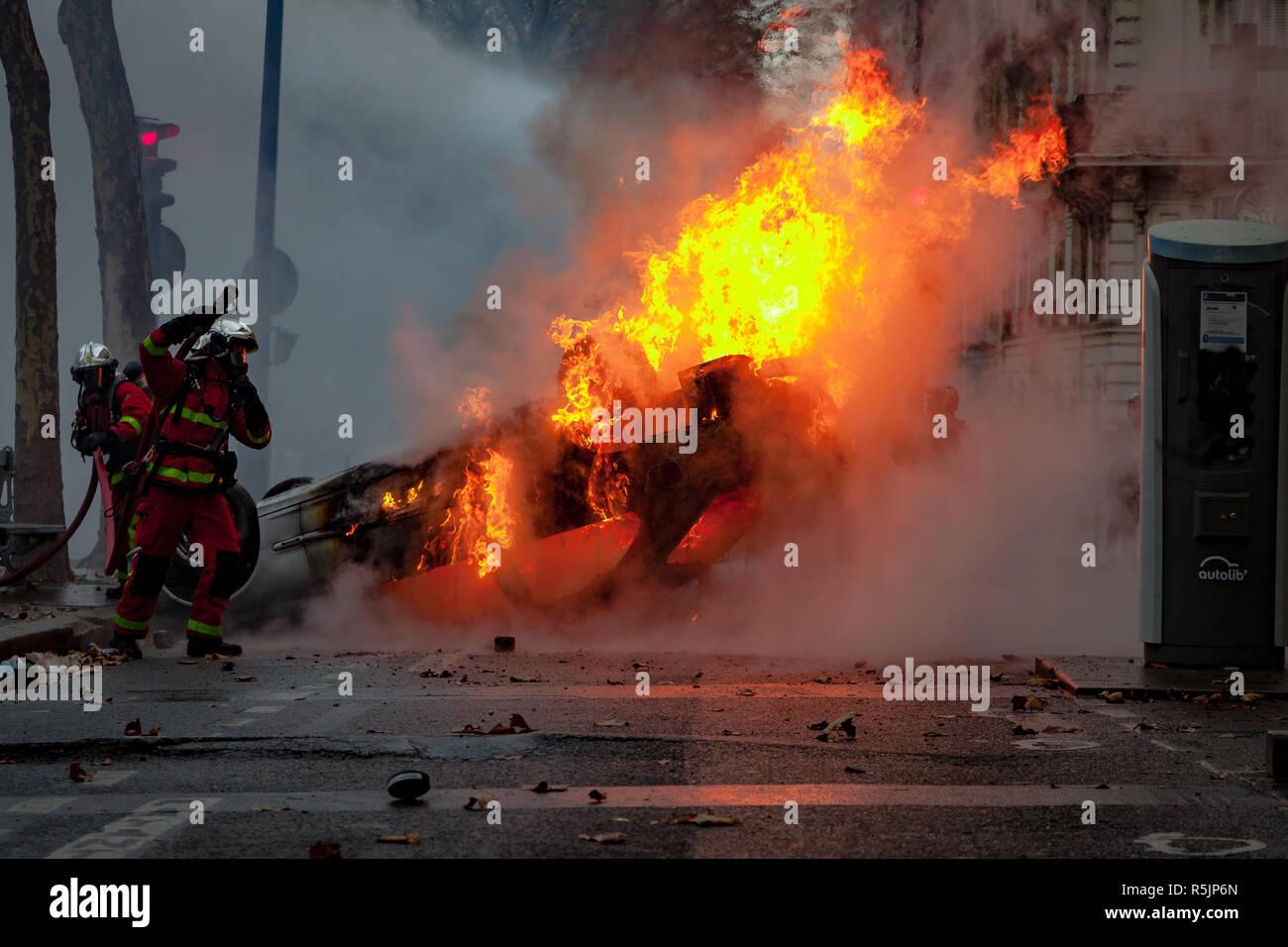 París, Francia. El 1 de diciembre, 2018. Los bomberos extenguishing un coche incendiado durante los chalecos amarillos protesta contra Macron político. Crédito: Guillaume Louyot/Alamy Live News Imagen De Stock