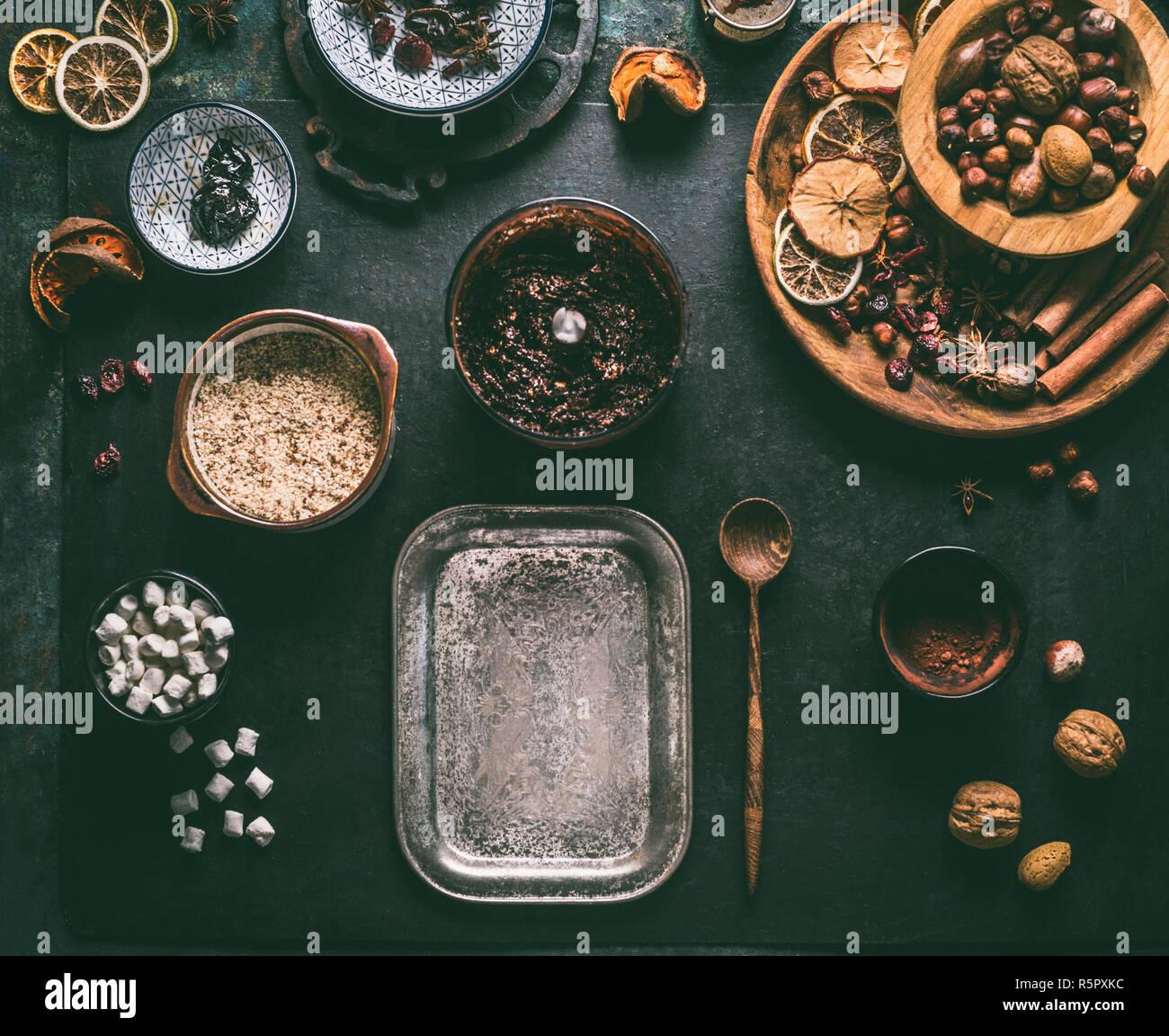 Preparación casera de vegan chocolate truffle praliné con frutos secos y nueces, mezcle los ingredientes en un fondo oscuro, vista superior. Dulces sanos. Ene Foto de stock