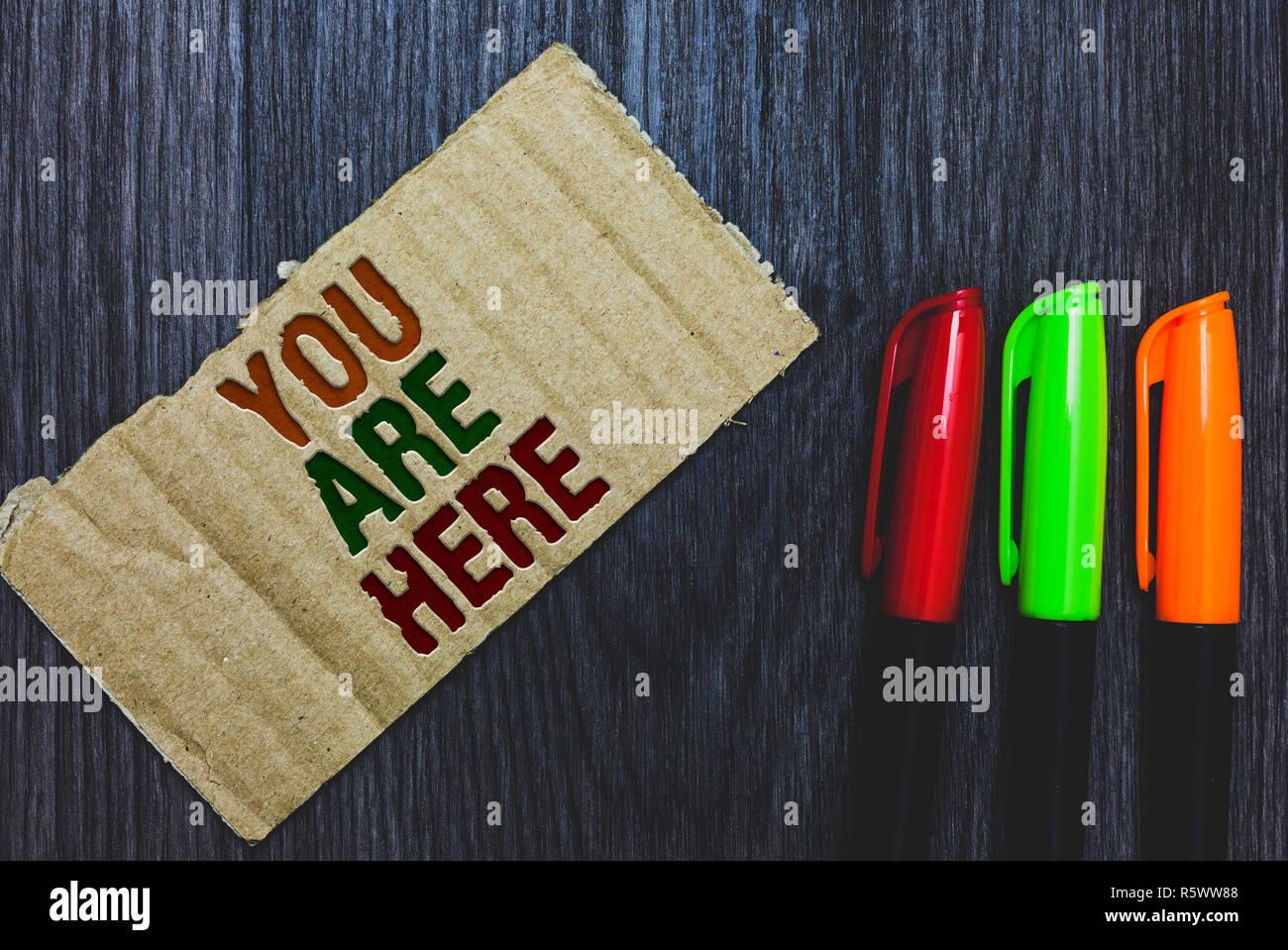 Escribir nota que muestra Usted está aquí. Exhibición fotográfica de negocios este es el punto de referencia de la ubicación del sistema de posicionamiento global con letras en cartón Imagen De Stock