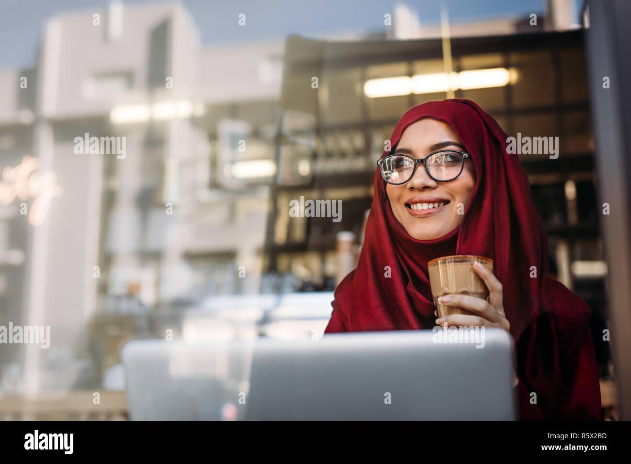 Hermosa mujer musulmana llevar el hijab y gafas relajantes en el cafe con una taza de café y mirando a otro lado con una encantadora sonrisa en su rostro. Feliz hija Imagen De Stock