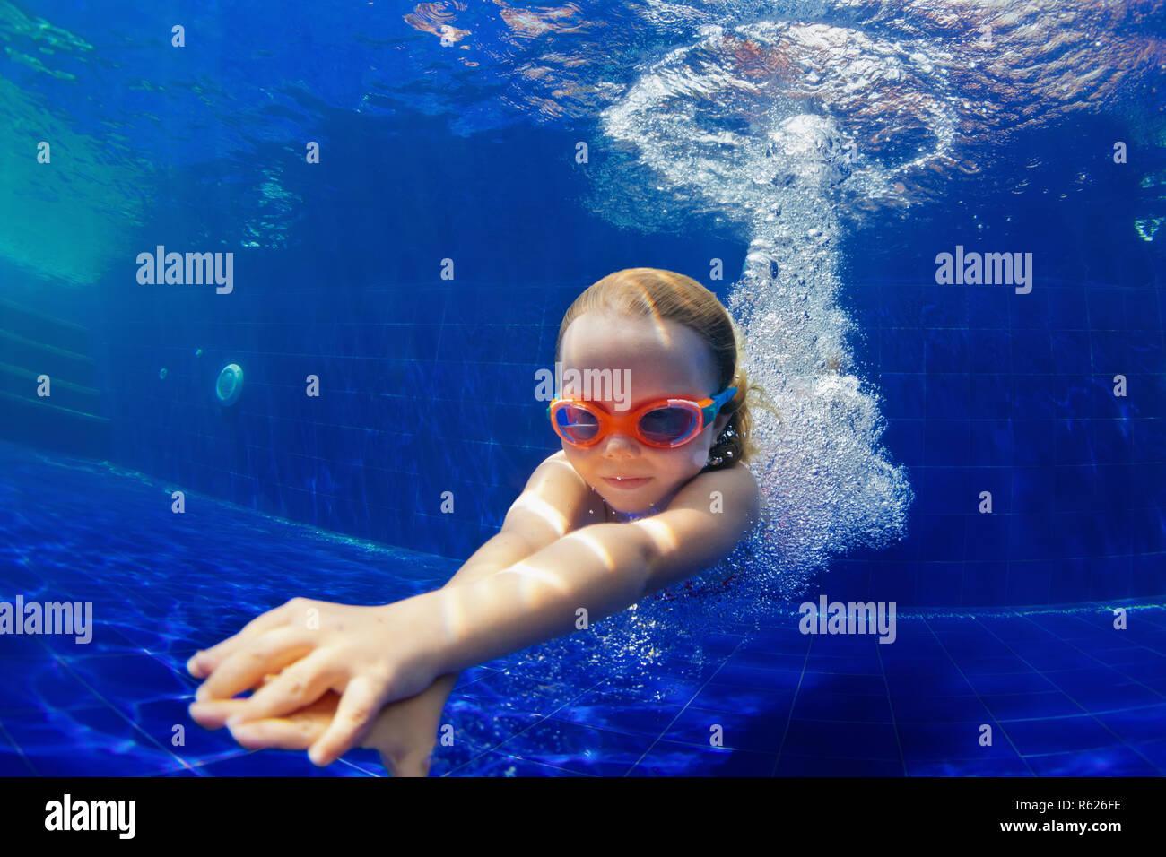 Familia feliz en la piscina. Niño sonriente en gafas de bucear, nadar en la piscina con la diversión - saltar profundidades submarinas. Estilo de vida saludable, la gente deporte acuático Foto de stock