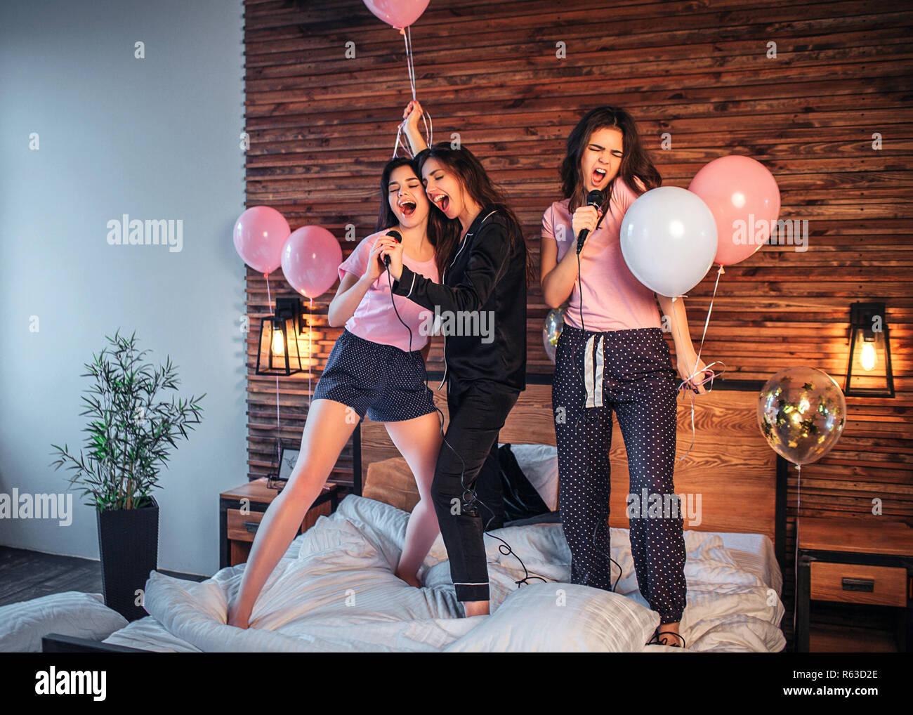 ad41d6a3e2d Las mujeres jóvenes de pie en la cama en la sala de fiestas. Tienen  micrófonos