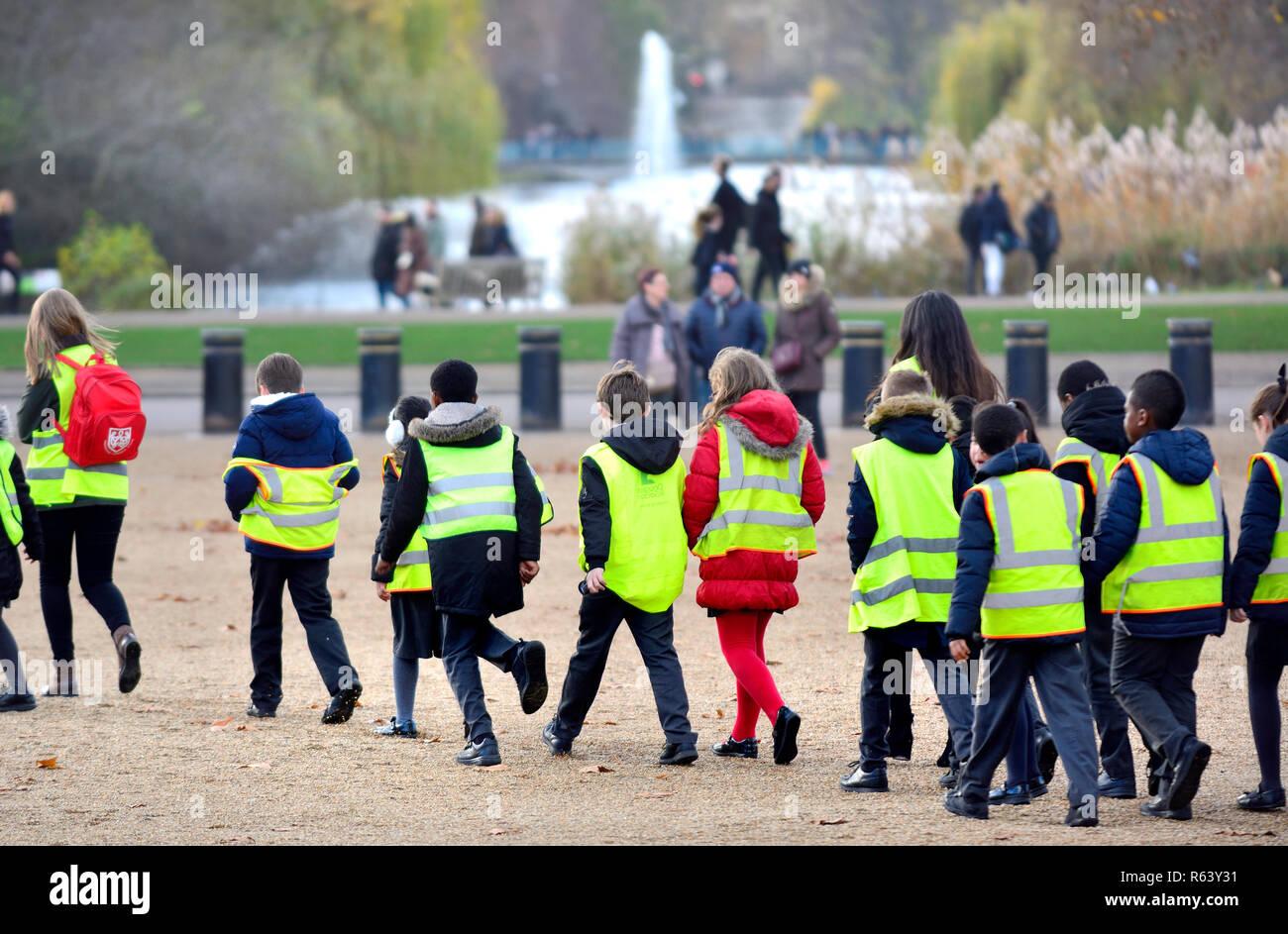 Los niños de escuela primaria en hi vis antibalas en una excursión escolar en desfile de guardias a caballo, en el centro de Londres, Inglaterra, Reino Unido. Imagen De Stock