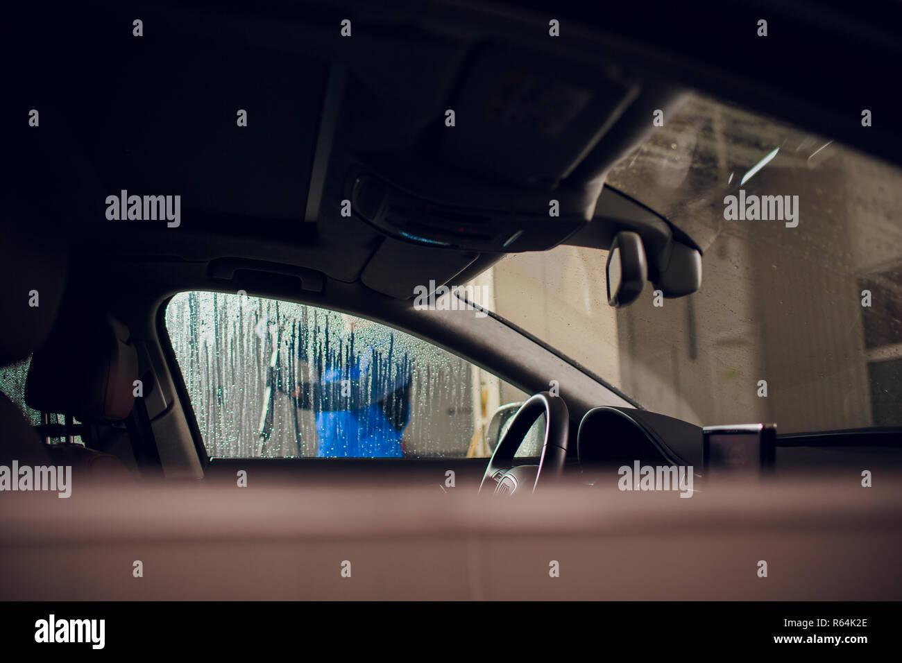 Hombre de lavado manual del automóvil Coche lavado self service,limpieza con espuma,presionó a agua. Lavado de coches en estación de autoservicio con alta presión blaster coche visto desde el interior de la ventana Imagen De Stock
