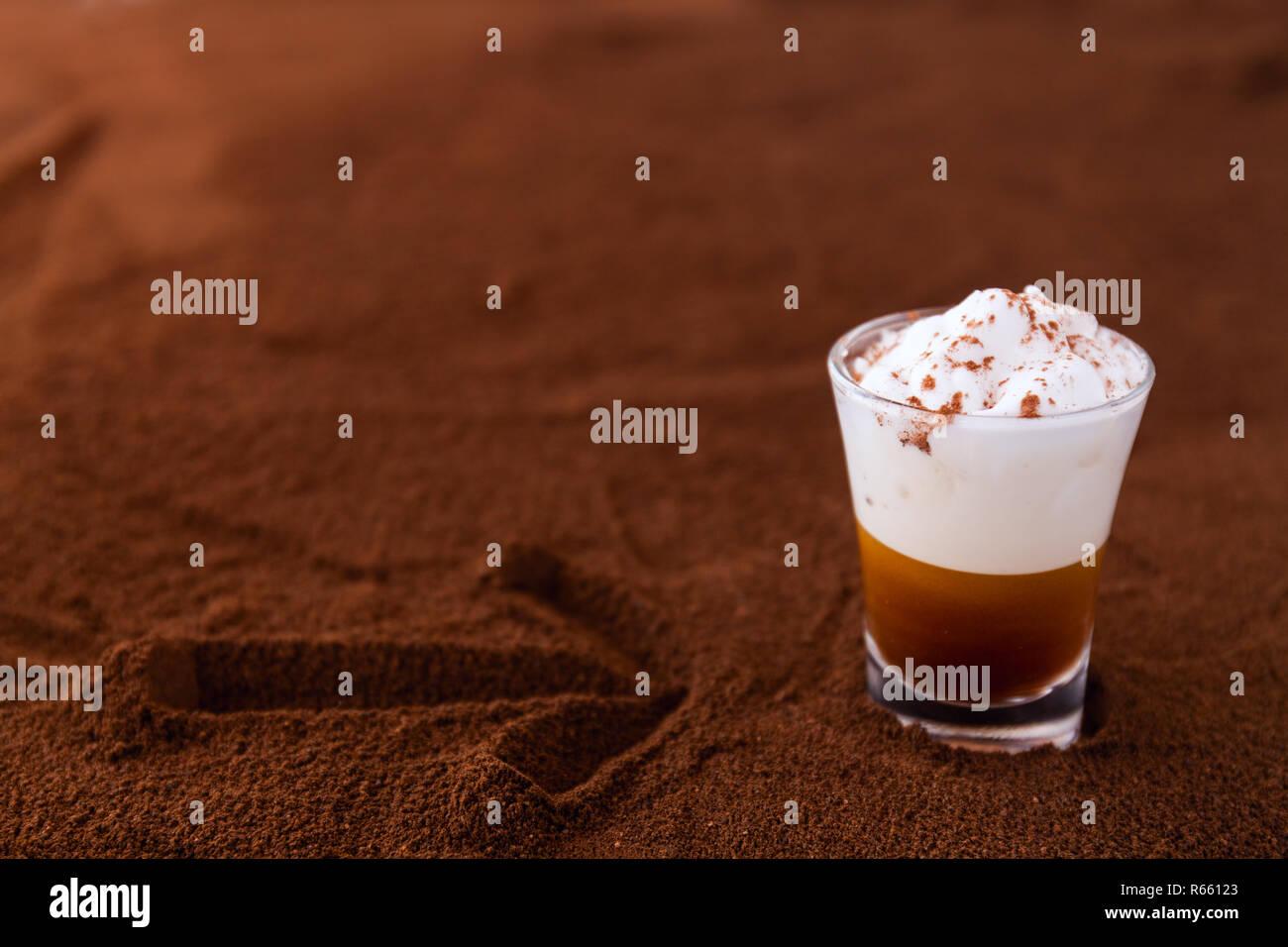 Poco taza de piccolo latte macchiato sobre una mesa cubierta con una flecha sobre el café molido como fondo Foto de stock