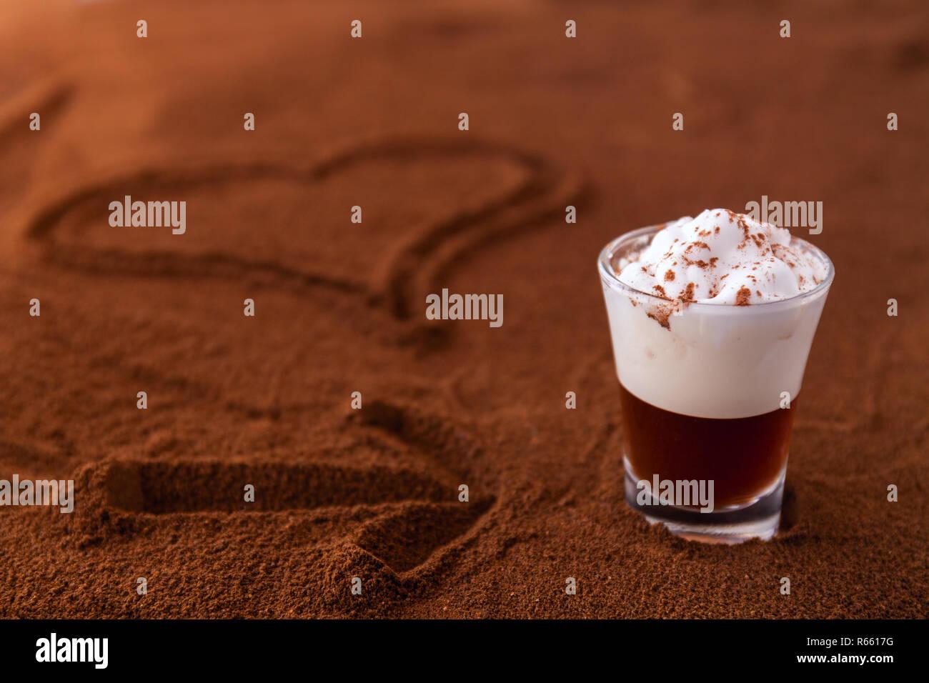 Poco taza de piccolo latte macchiato sobre una mesa cubierta con el corazón y la flecha sobre el café molido como fondo Foto de stock