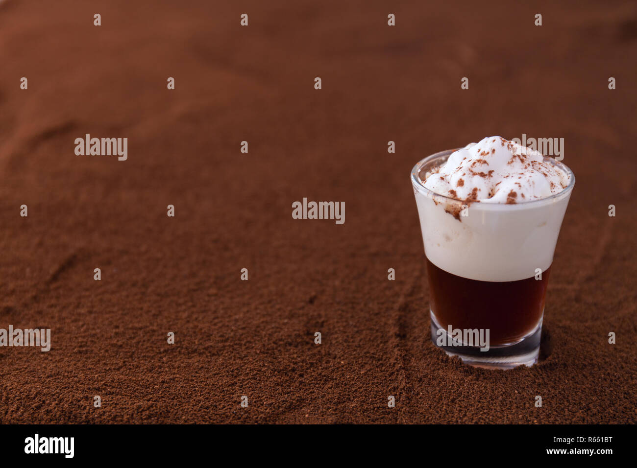 Poco taza de piccolo latte macchiato sobre una mesa cubierta con café molido como fondo Foto de stock