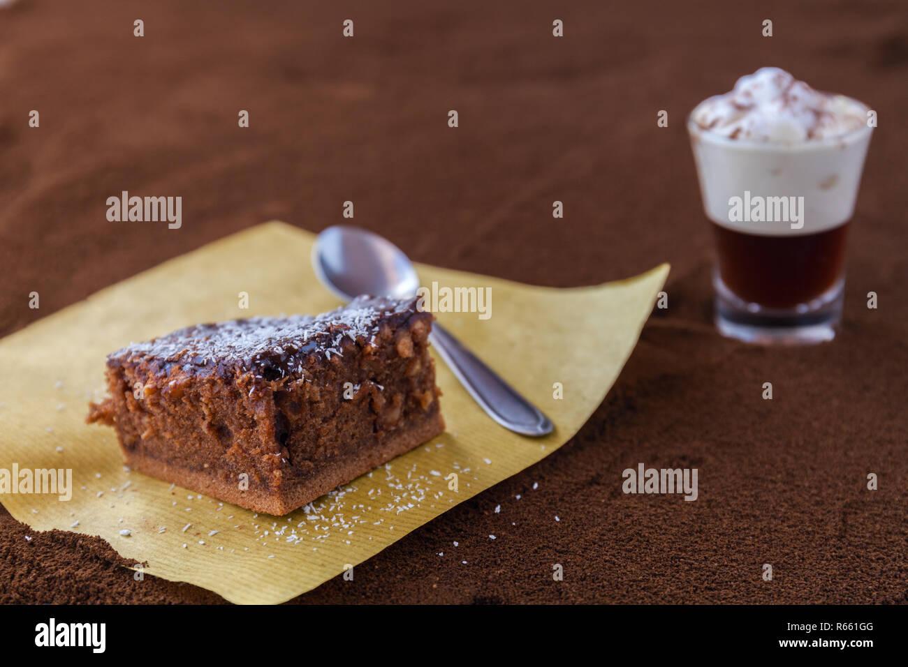 Poco taza de piccolo latte macchiato sobre una mesa cubierta con café molido como fondo y Brownie de chocolate con crema de cacao y virutas de coco Foto de stock