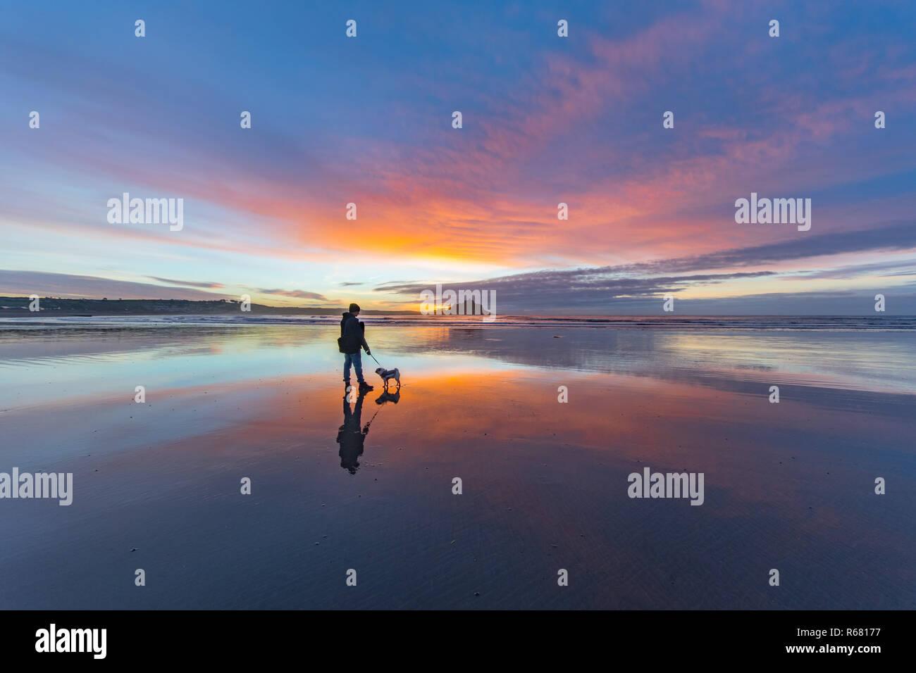 El hombre y su perro caminando por la playa en Longrock al amanecer con St Michaels mount en el fondo Imagen De Stock