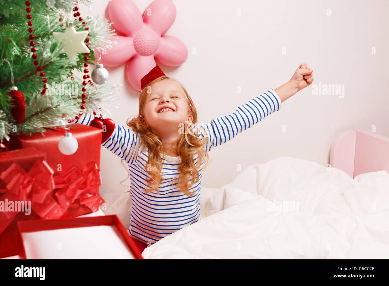 eb91041924 Poco feliz niño niña en santa hat tira arriba las manos sentado en la cama  después