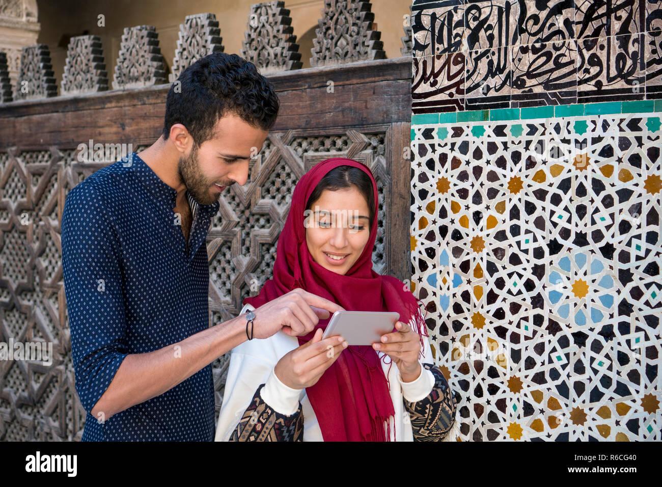 Pareja musulmana sonriendo mirando celular junto al muro marroquí decoración arabescos Imagen De Stock