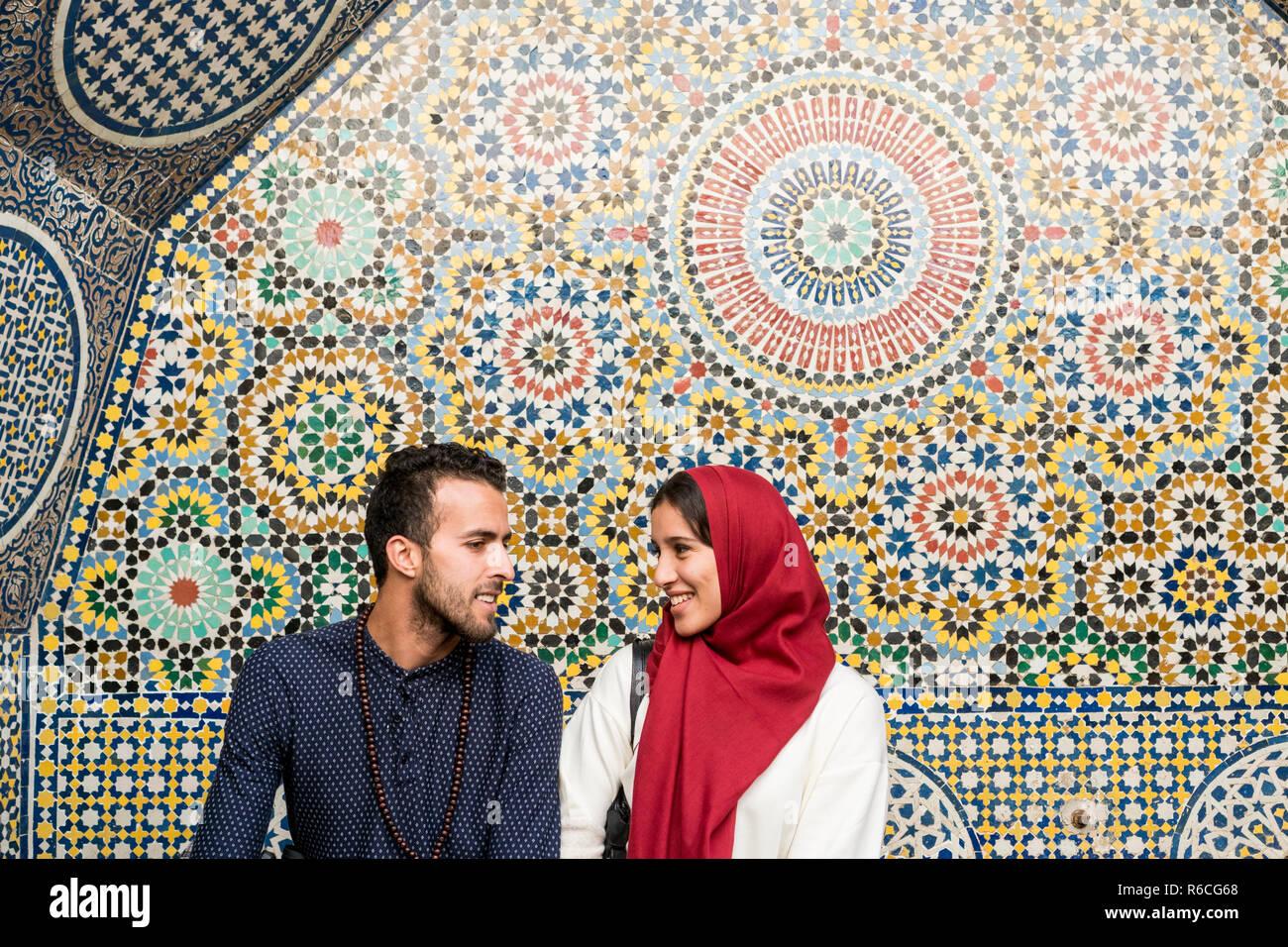 Joven pareja musulmana en relación hablando y sonriendo delante de arabesque decoración oriental Imagen De Stock