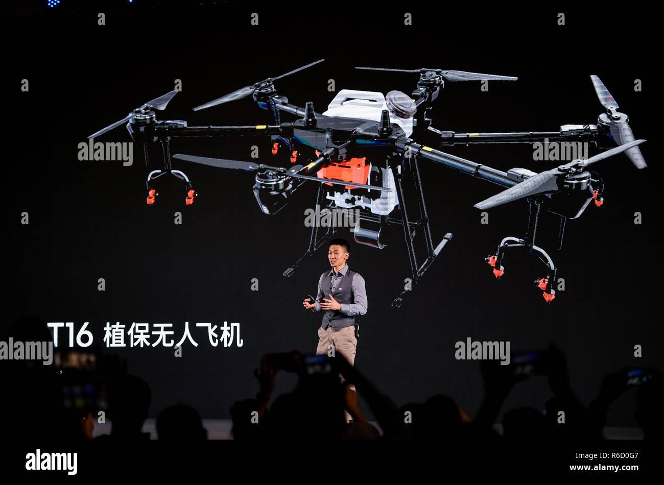 Shenzhen, en la provincia china de Guangdong. 4 dic, 2018. Chen Tao, director de ventas para el departamento agrícola del Dji, introduce el nuevo tipo de drone para cuidado agrícola T16 durante una conferencia de prensa en Shenzhen, en el sur de la Provincia china de Guangdong, 4 de diciembre de 2018. El recién liberado drone T16, con un tiempo de imágenes de radar DBF que puede controlar el entorno de los campos de cultivo, puede rociar pesticida sobre un área de 150 mu (alrededor de 10 hectáreas) en una hora, 67 por ciento más altos que los de generaciones anteriores. Crédito: Mao Siqian/Xinhua/Alamy Live News Imagen De Stock