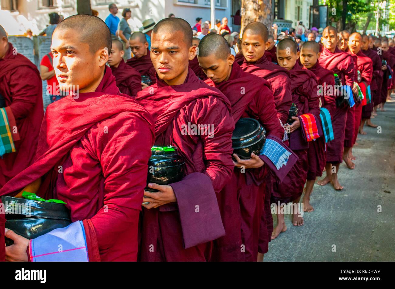 Novicios budistas caminar para recoger limosnas y ofrendas en Amarapura, cerca de Mandalay, Myanmar esta procesión se celebra cada día Imagen De Stock