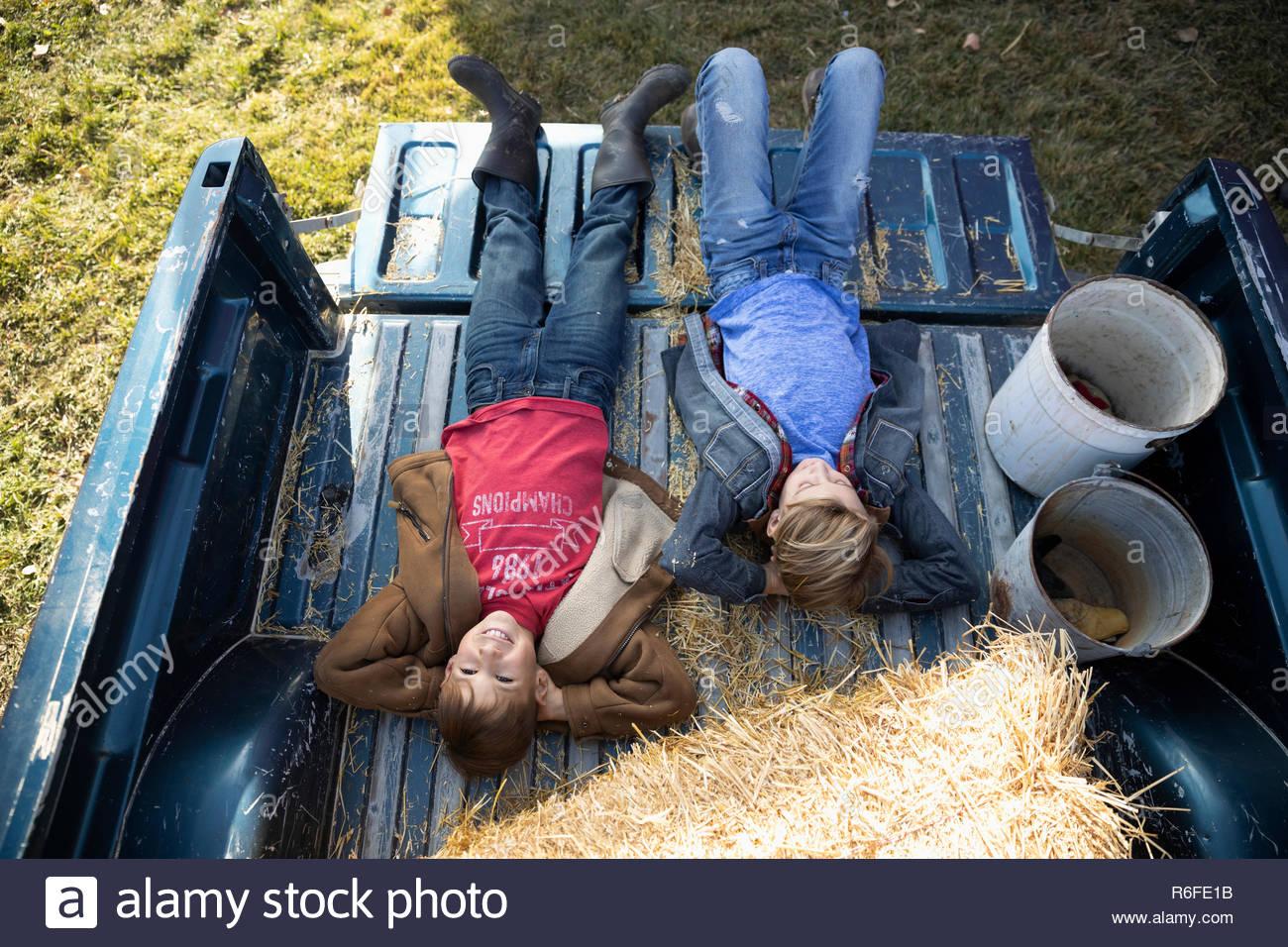 Vista desde arriba de la despreocupada hermanos relajante, sentando en la cama de una camioneta en la granja Imagen De Stock