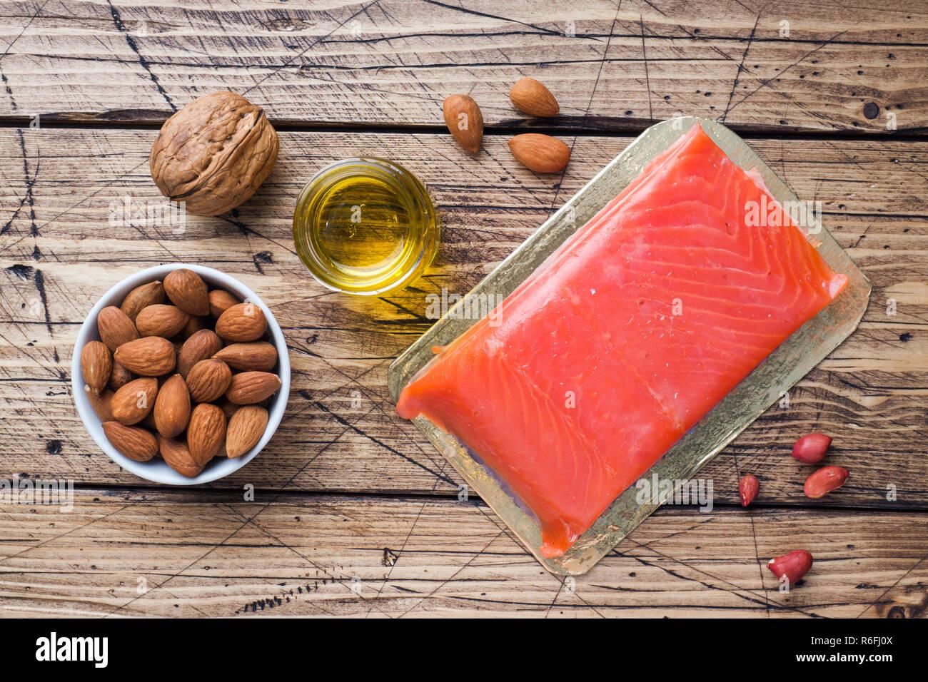 Concepto de alimentos saludables productos antioxidantes: pescado nueces y aceite sobre fondo de madera Imagen De Stock