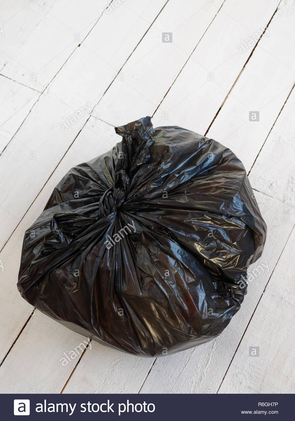 Bolsa de plástico negra llena de basura, aislado sobre fondo