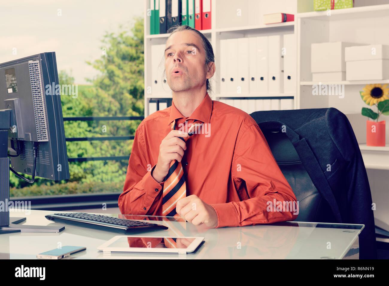 El hombre de negocios joven con ventilador en su escritorio en summerly o caliente Imagen De Stock