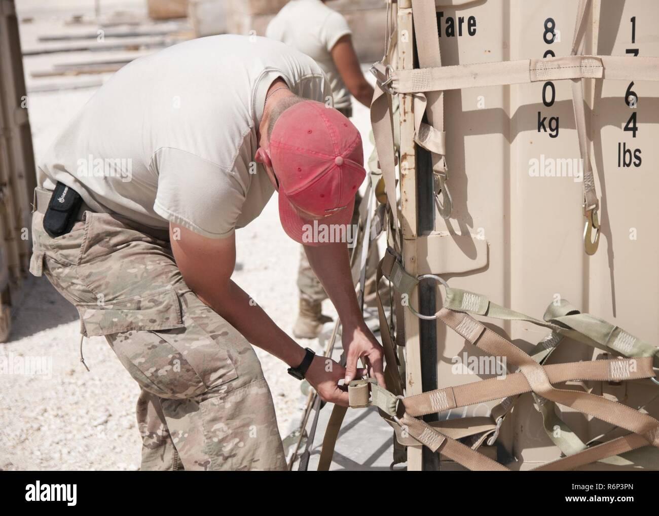 El Sgt. Brandon Krieger, de la 824ª Compañía de intendencia, asegura un contenedor con compensación de carga de entrega aérea en la base aérea de Al Udeid, Qatar, el 19 de abril de 2017. Operaciones de entrega aérea son esenciales para llevar suministros a las tropas en el Oriente Medio cuando los medios convencionales de transporte no son factibles. Foto de stock