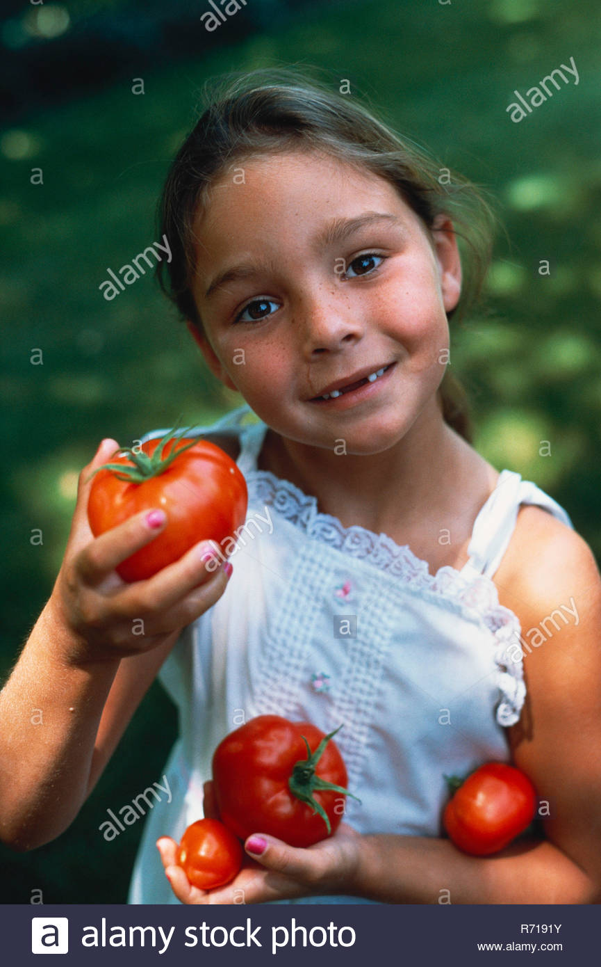 Las niñas sosteniendo los tomates Imagen De Stock