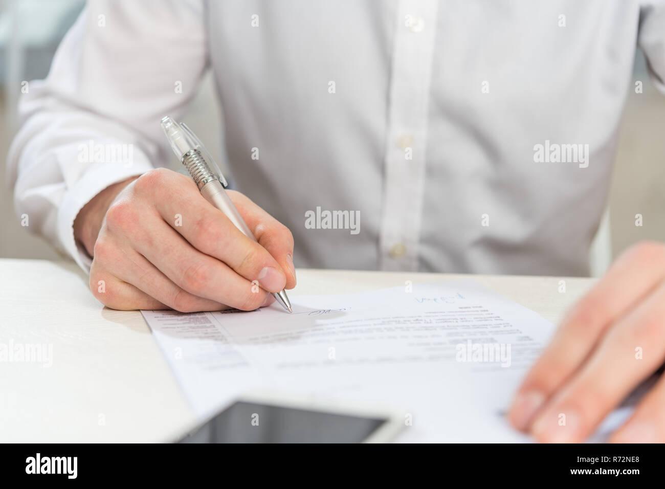 El hombre con la camisa blanca en una mesa con tablet pc Foto de stock