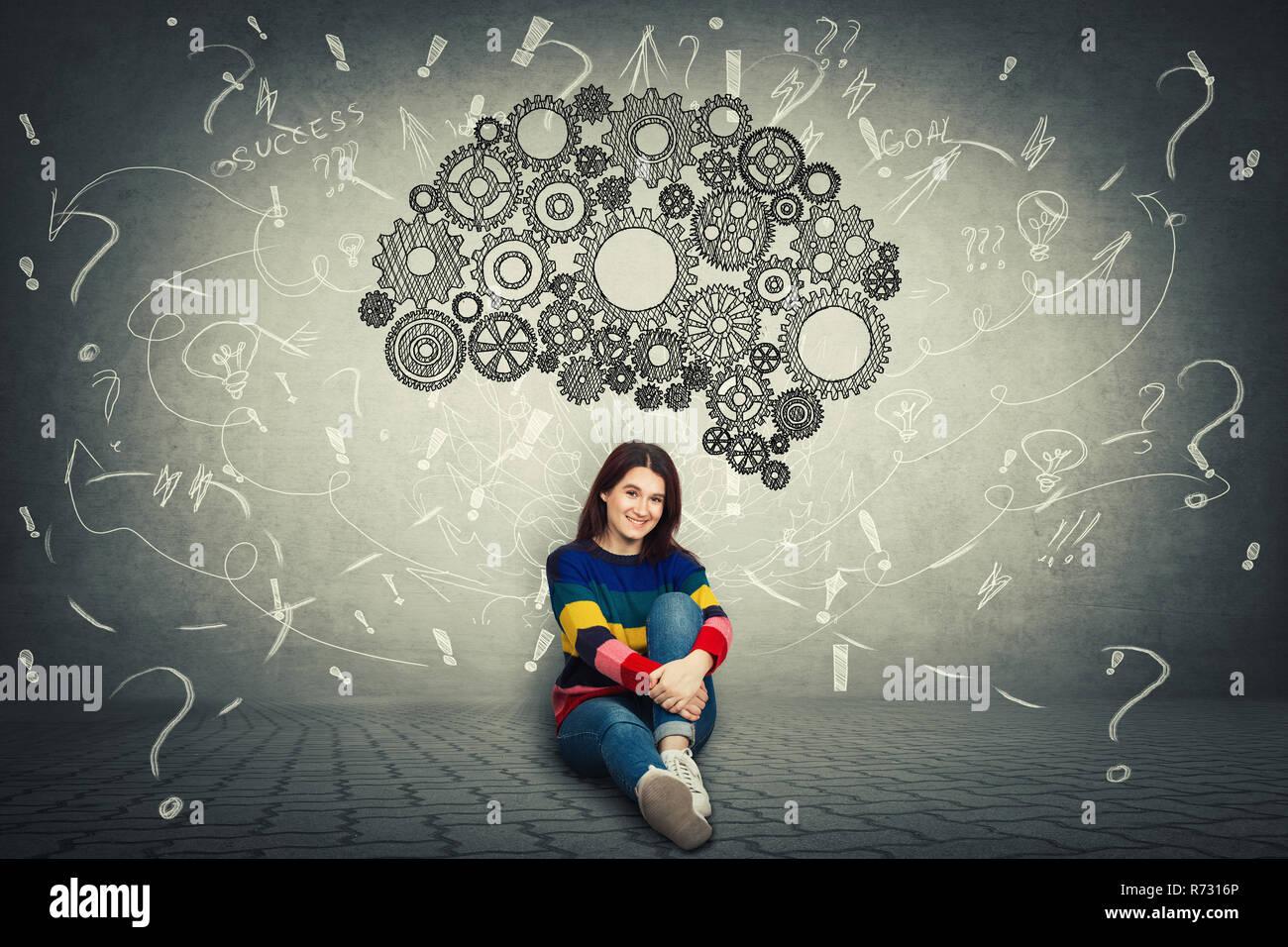 Bastante casual mujer sentada en el suelo y un enorme engranaje cerebro por encima de su cabeza, pensamiento positivo, signos de interrogación y el desorden como reflexiones alrededor. Concepto Foto de stock
