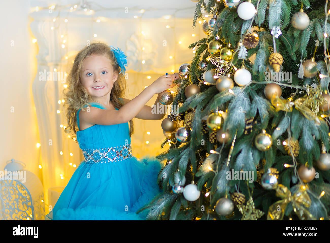 7b4d6d4f95 Hermosa joven en azul blanco elegante vestido de noche sentado en el suelo  cerca del árbol