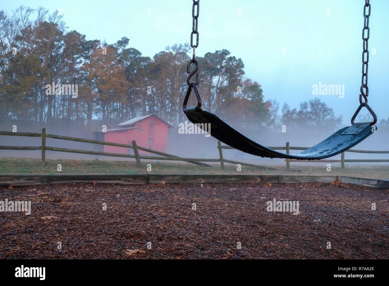Una solitaria y melancólica escena de un columpio vacío con un viejo granero rojo y roto una valla de madera en una fresca mañana de niebla. Lago Benson Park en Garner Nort Imagen De Stock