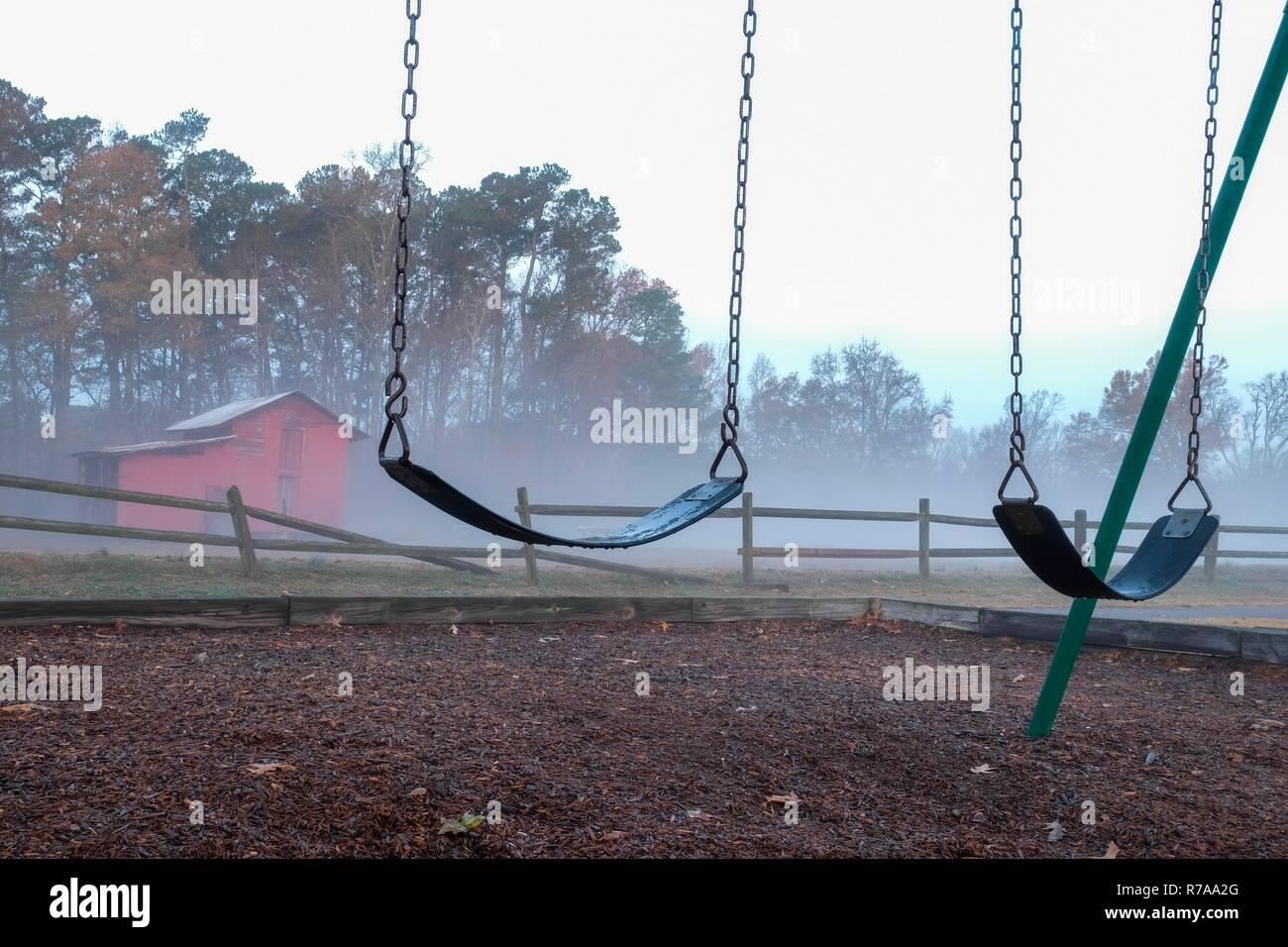 Una solitaria y melancólica escena de un par de columpios vacíos con un viejo granero rojo y roto una valla de madera en una fresca mañana de niebla. Lago Park en Benson Gar Imagen De Stock