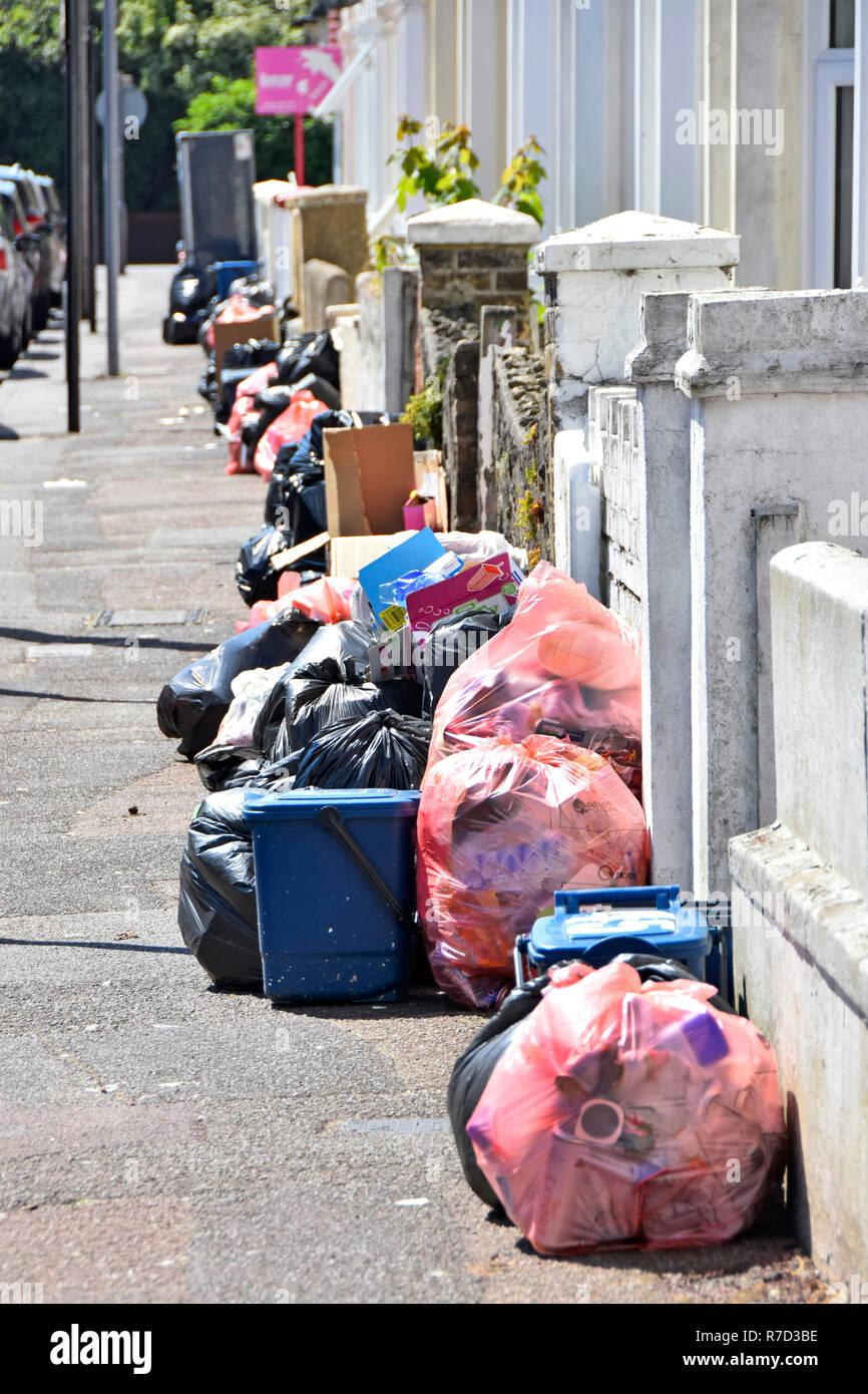 Escena de una calle de pavimento aplicado a la gestión de residuos adosados con bolsas de basura y contenedores fuera de recogida de residuos por el Consejo Southend, Essex UK Imagen De Stock