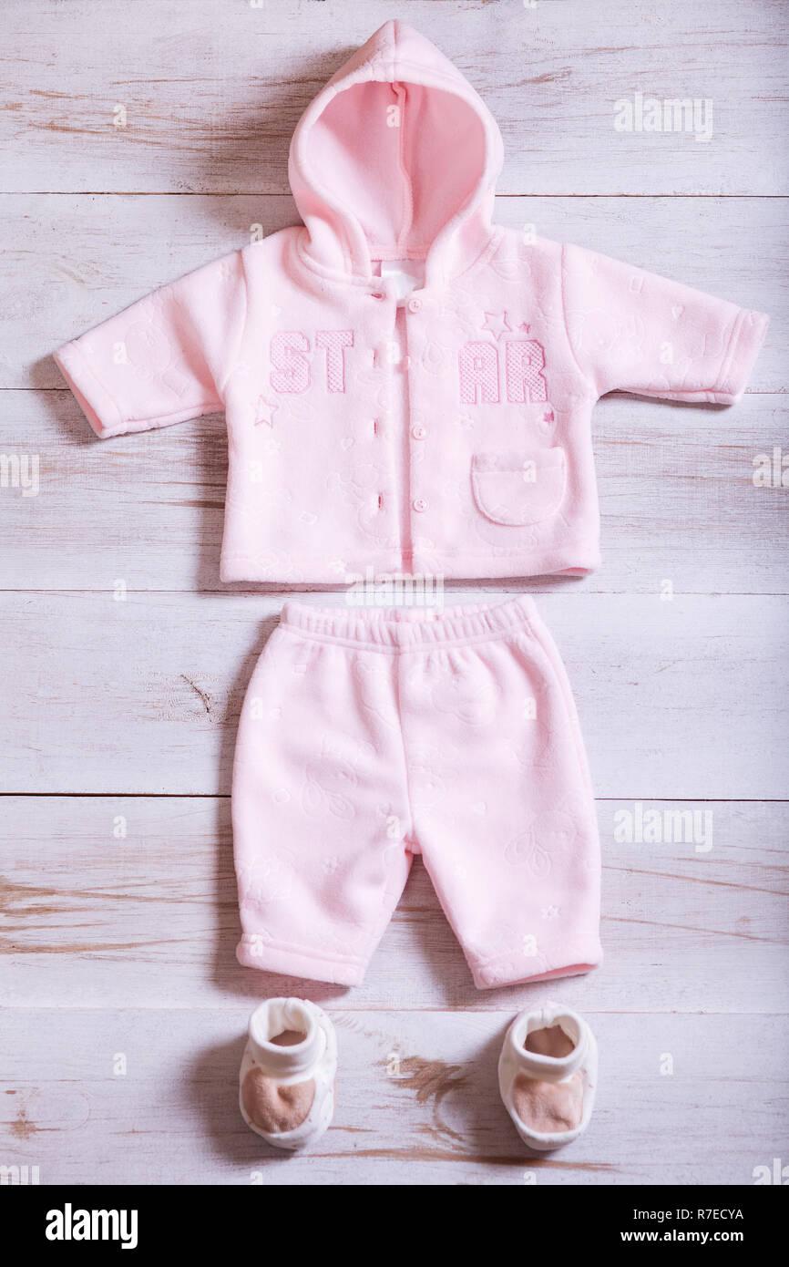 e8f558ea6 Ropa de bebé y accesorios en madera blanca tabla de fondo, Rosa niño recién  nacido