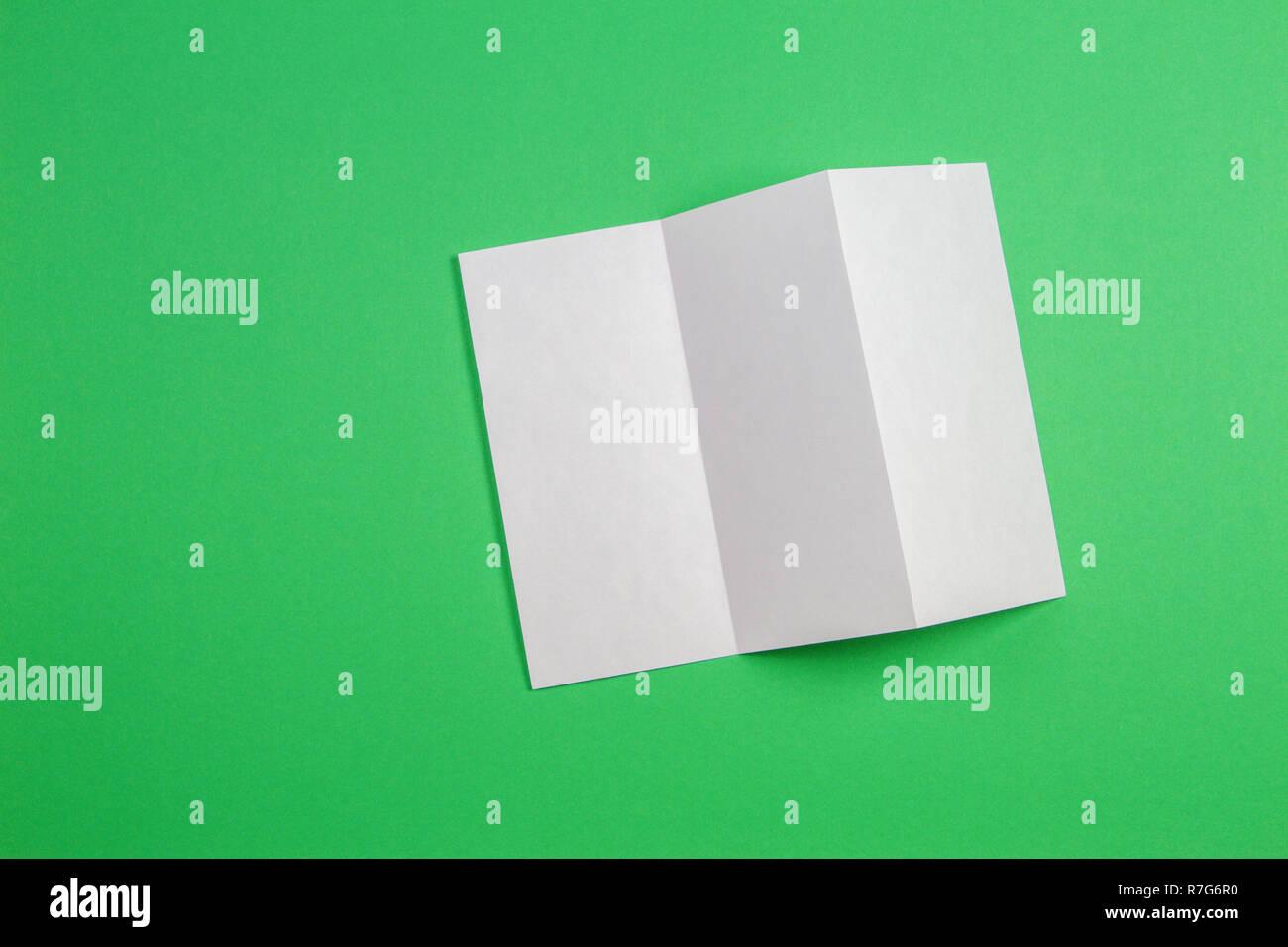 Boceto del folleto plegado triple blanco folleto sobre fondo verde. Foto de stock