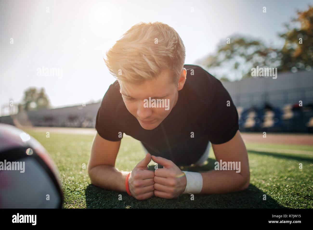 Joven rubia jugador de pie en posición de plancha sobre fútbol césped. Él está concentrada. Bola tumbado junto a él. Guy está solo. Foto de stock