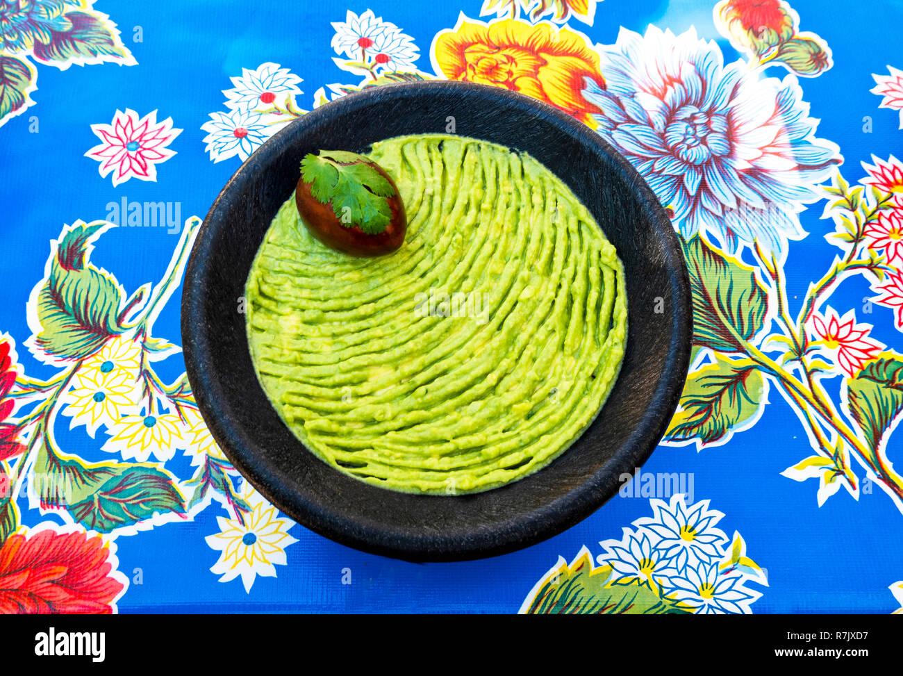 El guacamole en un recipiente de madera sobre una cubierta de mesa florido Imagen De Stock