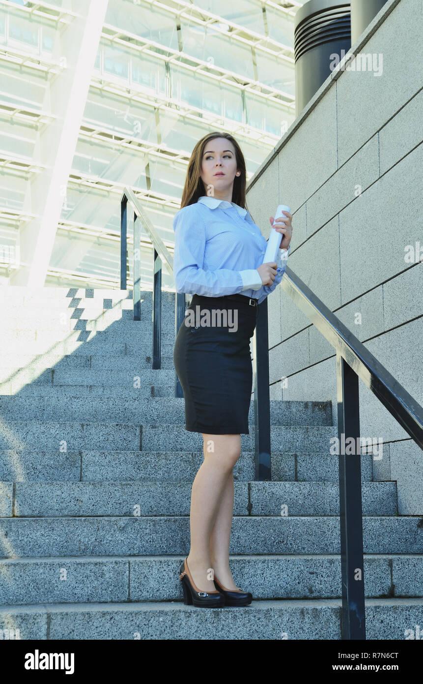 af55357e82 Joven y bella mujer de negocios de pie cerca de alta arquitectura en  zapatos y falda